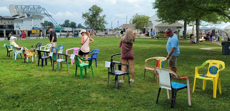 A photograph of the Conversation Chairs installation in River Park during the 2021 Mystic Outdoor Art Festival. 16 chairs face each other in two long rows as visitors read their descriptions.